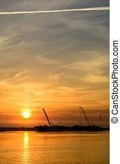 Two boats docking early in the morning near the pier. Horizontal view of a couple of boats loading up cargo in a summer morning over a sunrising sky on background.