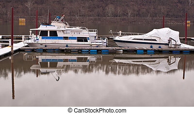 Two boats, dry docked on a river