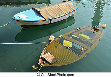 Two boats on berth, one is sinking