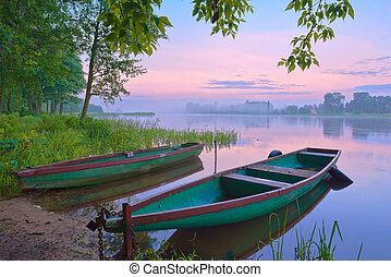 Two boats on the river. Foggy landscape.