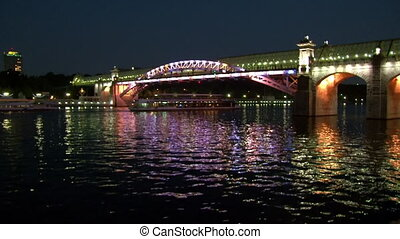 Two boats sail under the bridge in evening Moscow.