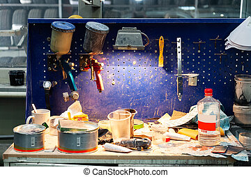 Two body paint gun sprayer red and blue installed on a workbench in a vehicle repair workshop next to another tool and lighting lamp. Industry in auto service