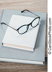 Two books and eyeglasses on table