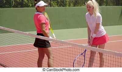 Two bored tennis players standing on court - Two attractive...