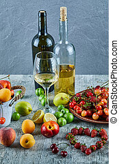 Two bottle and glass of wine on marble table with bunch of summer fresh fruits