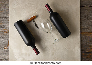 Two bottle of cabernet sauvignon wine on a gray tile surface on a rustic wood table