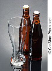 Two bottles of beer and an empty glass on a reflective surface