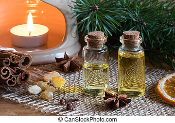 Two bottles of essential oil with cinnamon, star anise, frankincense and an aroma lamp