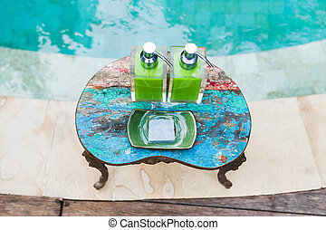 Two bottles of shampoo and handmade soap on old small vintage painted table