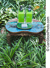 Two bottles of shampoo and handmade soap on vintage table in greens