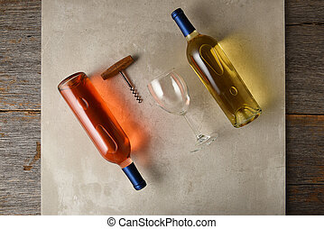 Two bottles of wine on a gray tile surface on a rustic wood table