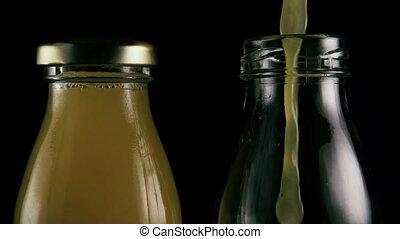 Two bottles on a black background with juice. Slow motion