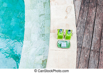 Two bottles shampoo and handmade soap on edge of pool. Spa concept