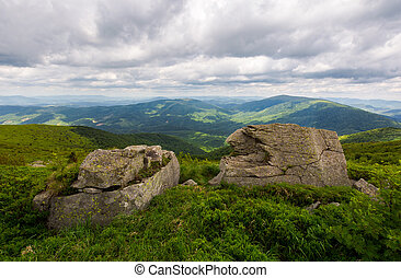 two boulders on the grassy hill. mountain range in the...