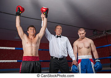 two boxer men standing in ring. referee lifting winner hand...