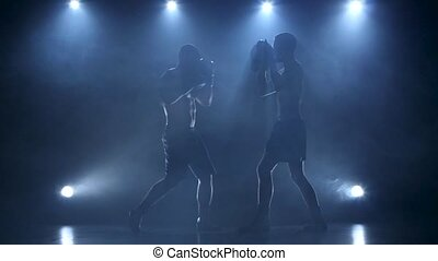 Two boxers help each other in training. Silhouette, slow motion
