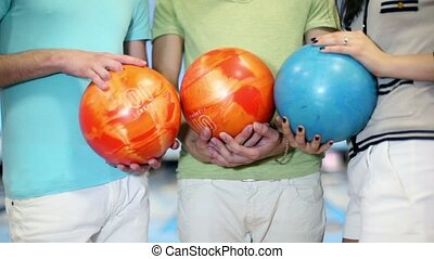 Two boy and one girl hold bowling balls, closeup view