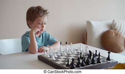 Two boy playing chess in light room. Two brothers playing chess.