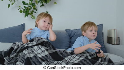 Two boys, 4 and 2 years old, are watching TV sitting on the...