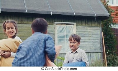 Two boys and girl fight pillows in yard country house. Childhood. Man in costume