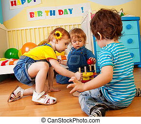 Two boys and girl playing with toy pyramid puzzle