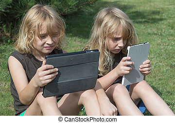 Two boys are looking to their tablets outdoors
