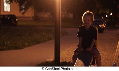 Two boys at playground enjoying at night in open air. Boys...