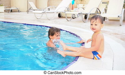 two boys brother bathe in the swimming pool at the resort