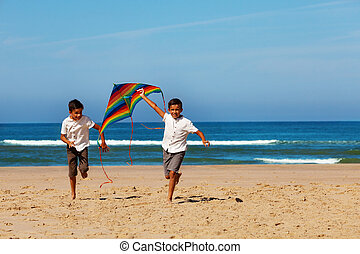 Two boys brothers run on the beach with kite