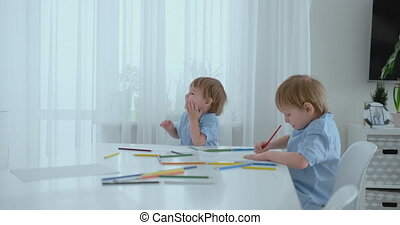 Two boys brothers sit at a table in the living room and draw with pencils on paper. Mom comes up and hugs the boys, smiling and stroking his head. Praises and helps to make the task