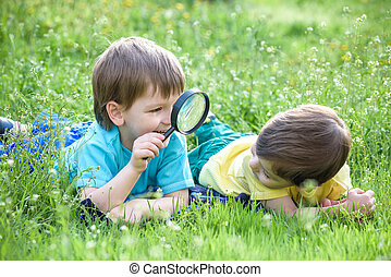 Two boys brothers with magnifying glass outdoors.