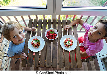Two boys eat for Breakfast Viennese waffles with ice cream and strawberries