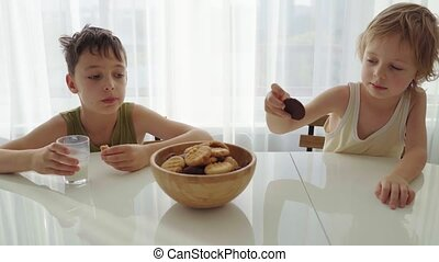 Two boys eating homemade cookies with milk at home kitchen