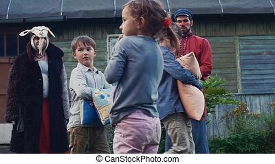 Two boys fight pillows in yard of country house. Childhood. Man play balalaika.