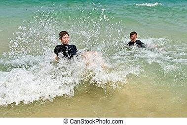 two boys having fun in the ocean - two boys having fun in...