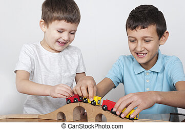 boys having fun playing with a wooden train