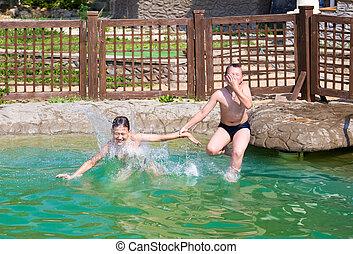 Two boys jump into the pool. Horizontal image