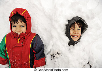 Two boys laying in snow
