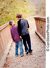 Two boys looking at each other on a bridge
