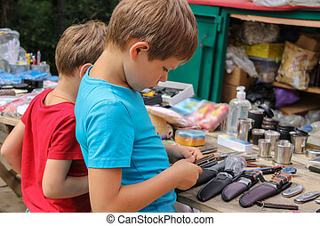 Two boys looking at souvenirs in the market of Schodnica, Ukraine