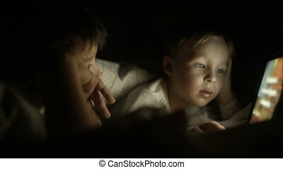Two boys lying in bed at night and using pad
