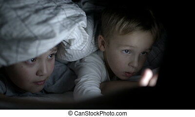 Two boys lying in bed at night watching movie on pad
