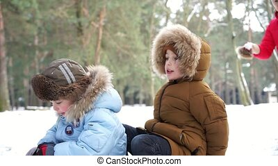 Two boys on sledge riding down and their mother drop snow ball