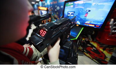 boys play interesting space game with gun on screen - two...