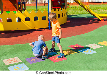Two boys playing hopscotch outdoors in the summer