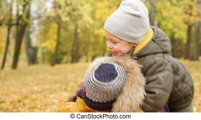 Two boys playing in autumn park