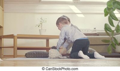 Two boys playing stuffed toys - Two boys sitting on the...