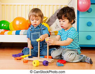 Two boys playing with pyramid blocks
