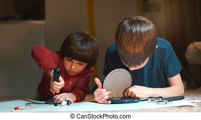 Two boys repair electrical equipment lying on the floor. The...