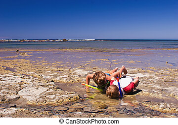 Two boys explore the shallow rock pools close up. Te Angiangi Marine Reserve in Central Hawkes Bay, New Zealand